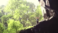 Woman jumps for joy in a cave's light opening video