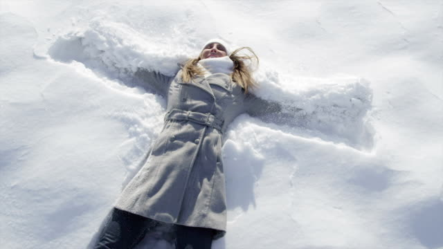 SLOW MOTION: Woman jumps into snow and makes an angel video