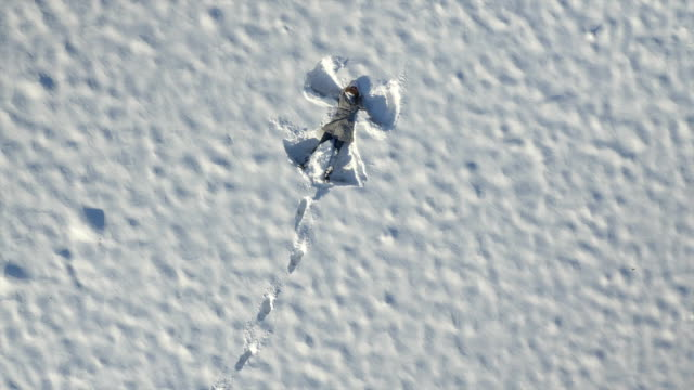 AERIAL: Woman jumps into the fresh snow and makes an angel video