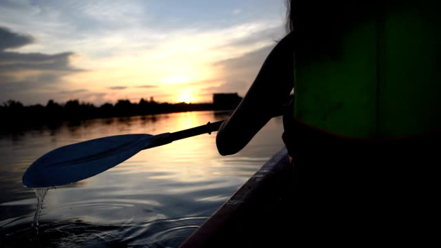 Woman kayaking on the lake in twilight video