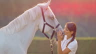 SLO MO Woman kissing horse on nose in meadow video