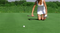 Woman kneels at the golf video