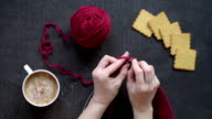 Woman knitting while drinking coffee video