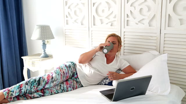 Woman laying on a bed using laptop video