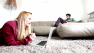 Woman laying on carpet looking at laptop while man sitting on couch reading book video