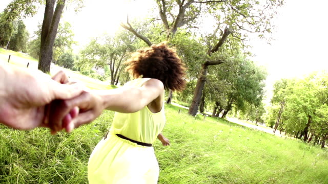 Woman leading boyfriend through park video