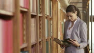 TU DS Business woman leafing through a book in the library video