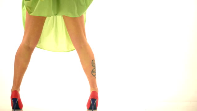 Woman legs with tatoo and high heels on white dots video