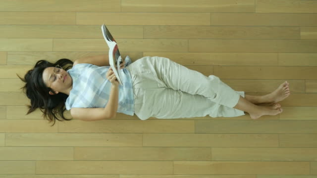 woman lie down  reading a book in home library video