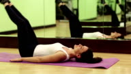 Woman lies on the mat and pumps abdominal muscles. Woman trains in gym video