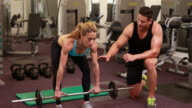 Woman lifting barbell with her trainer at crossfit session video