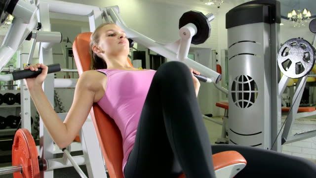 woman lifting too much weight on chest press machine in health fitness club video