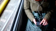 Woman listening music on her smart phone in trolley bus video
