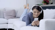 Woman listening music wearing headphones looking at her smartphones video