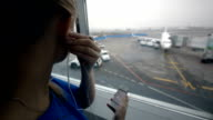 Woman listening to music by the window at airport video