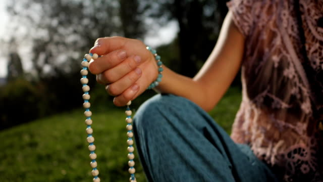 Woman, lit hand close up, counts Malas, strands of wooden beads used for keeping count during mantra meditations. Buddhism. Girl sitting in the park at summer. Slow motion video