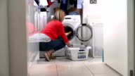 Woman Loading Clothes Into Washing Machine video