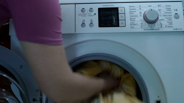 Woman loading the dirty laundry in the washing machine and close the lid of the drum. A woman presses a button on the control panel. She is specifies a program of laundry washing and the washing machine starts to work. video