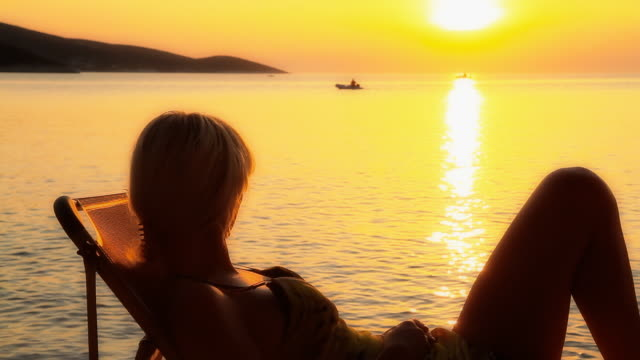 HD DOLLY: Woman Looking A Motor Boat At Sunset video