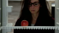 woman looking annoyed at apple in fridge video