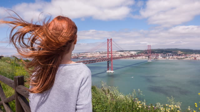 Woman looking at 25 de Abril bridge in Lisbon, Portugal video