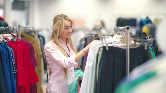 Woman looking at clothes on rail in clothing store. Attractive young woman shopping video