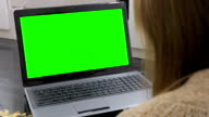 Woman looking at laptop with green screen video
