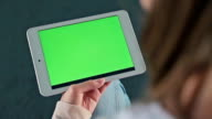Woman looking at tablet with green screen video