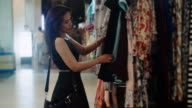 woman looking at the clothes in a boutique. video