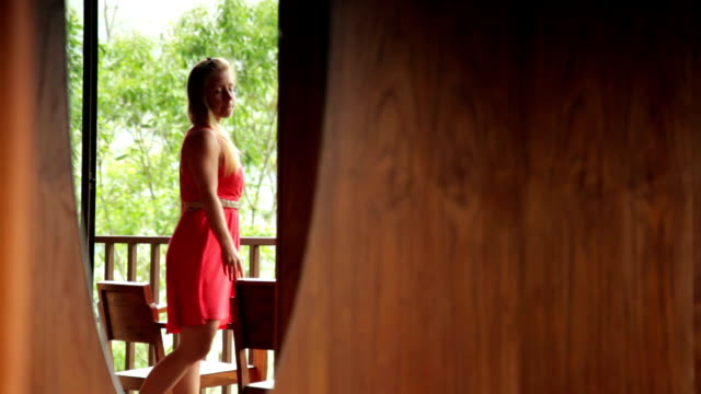 Woman looking at view from her Balcony. Vacation in Thailand. video