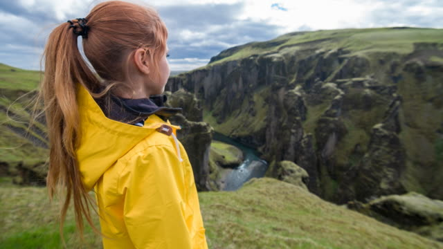 Woman looking down at Iceland's canyon video