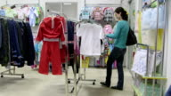 Woman looking for clothes in clothing store video