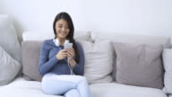 Woman looking her social apps while sitting on couch video
