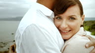 Woman looking into camera while in her loved ones embrace video