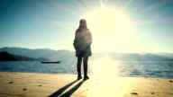 Woman looking sunrise in the lake video