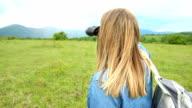 Woman looking though binoculars at mountain video