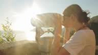 Woman looking through binoculars. video