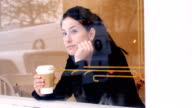 Woman looking through window while having coffee video