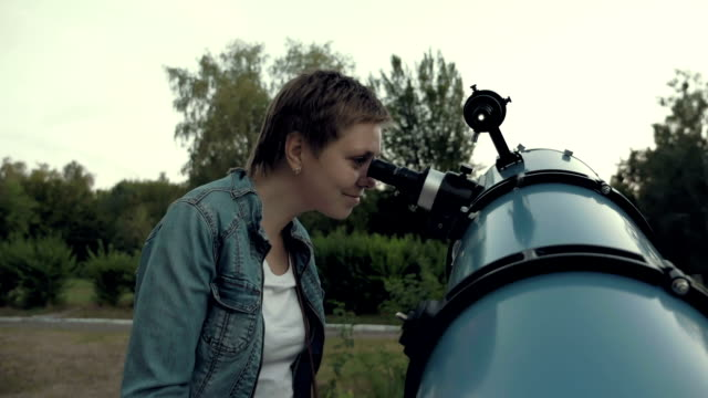 Woman looking to the moon through telescope video