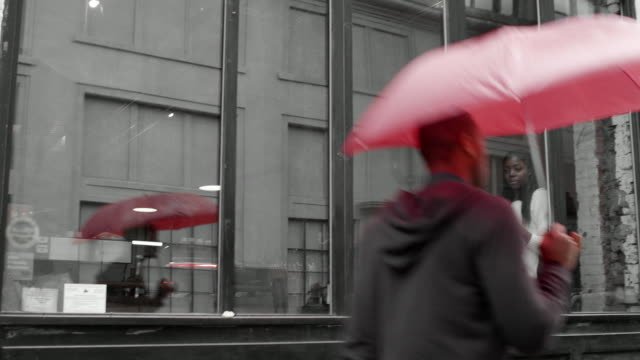 A woman looks out of a window while drinking coffee and then a man holding a red umbrella walks past video