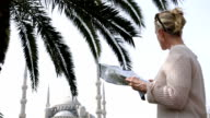 Woman looks out over Blue Mosque, reads map, Istanbul video