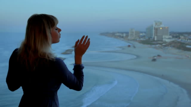Woman looks out the window at seashore video
