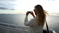 Woman looks out to sea from deck of ship, takes picture video