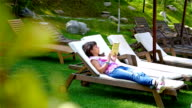 Woman lying and reading a book in the garden video