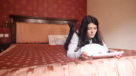 Woman lying in bed and reading on the digital tablet. video