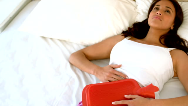 Woman lying in bed with cramps video
