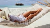 Woman lying in hammock near the sea. video