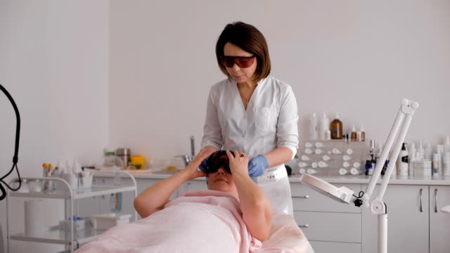 Woman lying on a table with protect glasses on eyes getting a laser skin treatment in healthy beauty spa salon video