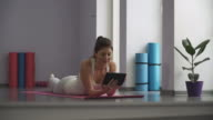 Woman lying on a yoga mat and looking at the tablet video