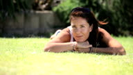 Woman lying on lawn pulling faces video